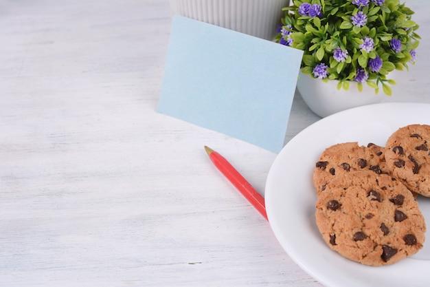 Cartão de papel vazio com caneta vermelha e cookies