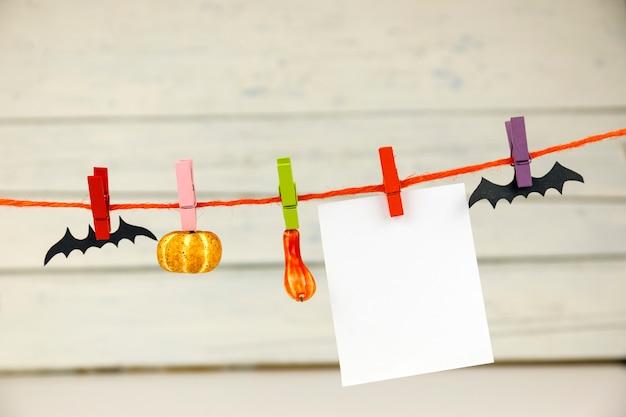 Cartão de papel vazio pendurado em prendedores de roupa com morcegos e abóboras decorativas