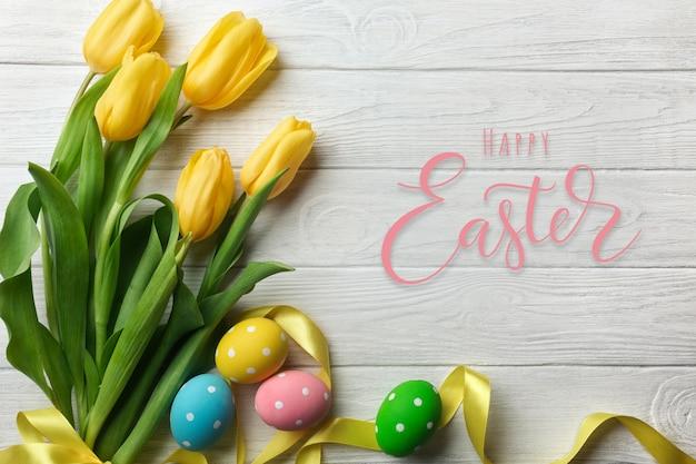 Cartão de páscoa com buquê de flores de tulipa e ovos de páscoa. vista superior sobre a mesa de madeira com espaço para suas saudações