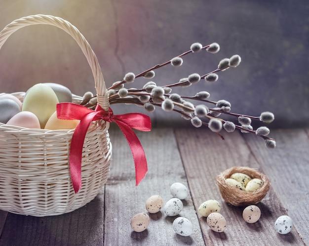Cartão de páscoa com cesta de páscoa, ovos de páscoa coloridos e galhos de salgueiro na mesa de madeira.