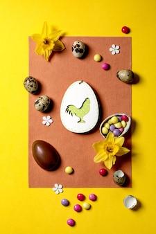 Cartão de páscoa com decorações de madeira, doces de chocolate e ovos