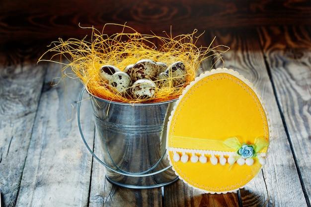 Cartão de páscoa e ovos de codorna em um balde