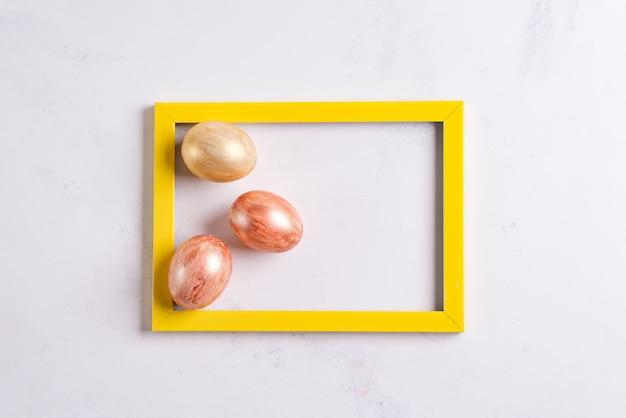 Cartão de páscoa e ovos de ouro na moldura amarela sobre um fundo de mármore