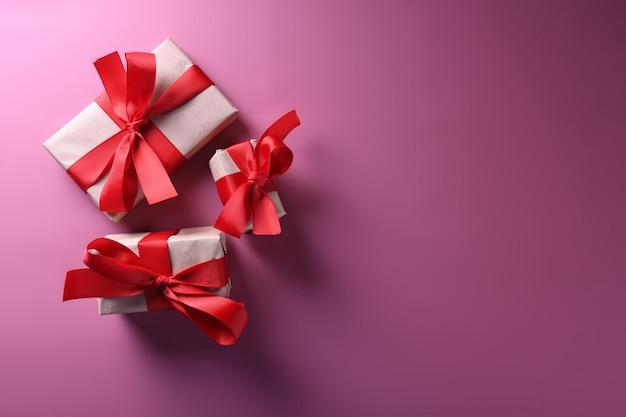 Cartão de plano de fundo dia dos namorados amor símbolos, decoração vermelha com caixas de presentes. vista superior com cópia espaço e texto.