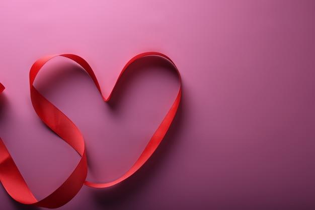 Cartão de plano de fundo dia dos namorados amor símbolos, decoração vermelha com coração em fundo rosa. vista superior com cópia espaço e texto.