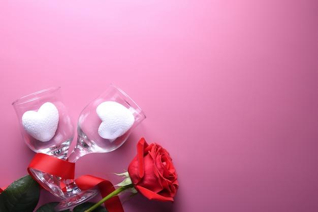 Cartão de plano de fundo dia dos namorados amor símbolos, decoração vermelha com óculos no fundo rosa. vista superior com cópia espaço e texto.
