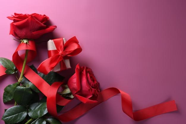 Cartão de plano de fundo dia dos namorados amor símbolos, decoração vermelha com rosas. vista superior com cópia espaço e texto.