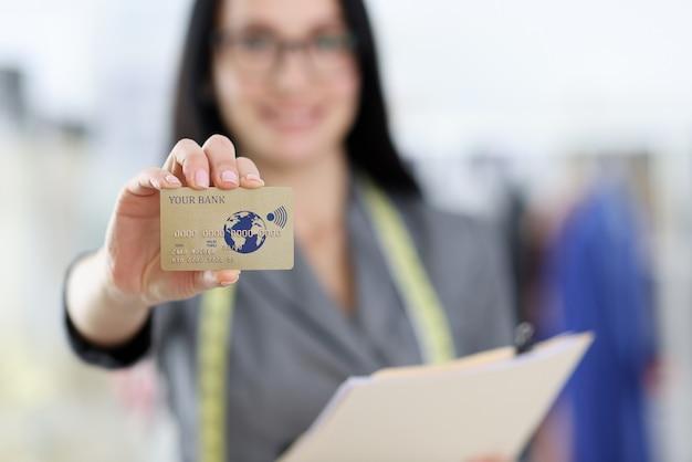 Cartão de plástico do banco de crédito na mão de uma mulher. conceito de pagamentos com cartão bancário