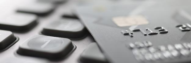 Cartão de plástico do banco deitado na calculadora closeup conceito de pagamento de impostos