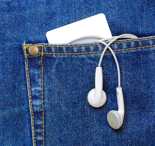 Cartão de plástico em branco e fones de ouvido pendurados no bolso da calça jeans.