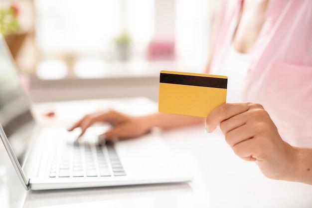 Cartão de plástico na mão de jovem cliente contemporâneo da loja online inserindo dados pessoais ao fazer o pedido