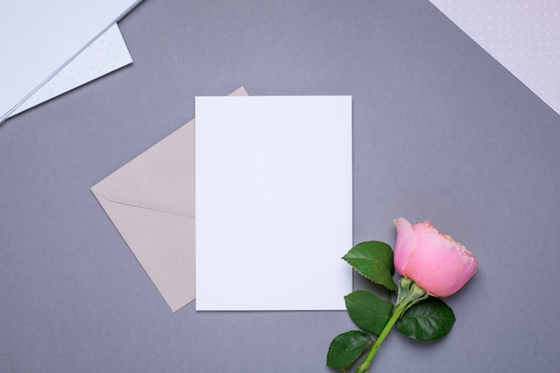Cartão de presente e envelope com rosa rosa em cinza