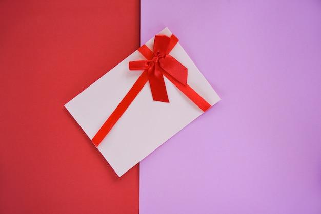 Cartão de presente no fundo vermelho e rosa cartão de presente decorado com laço vermelho da fita