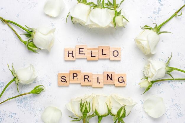 Cartão de primavera com rosas brancas e flores, vista superior