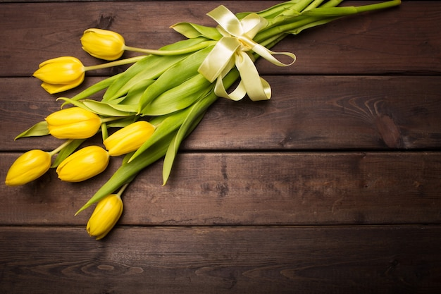 Cartão de primavera: tulipas amarelas sobre um fundo escuro de madeira. vista de cima, plano.