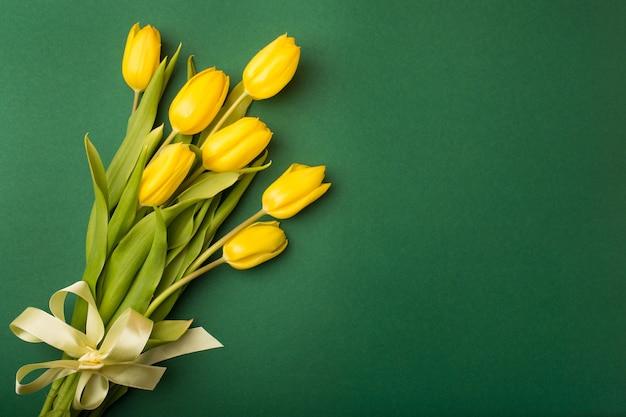Cartão de primavera: tulipas amarelas sobre um fundo verde. vista de cima, plano.
