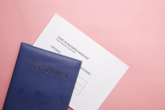 Cartão de registro de vacinação e passaporte em fundo rosa
