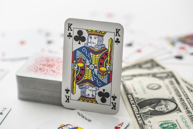 Cartão de rei com pilha de outros cartões ao lado de notas de banco de um dólar.