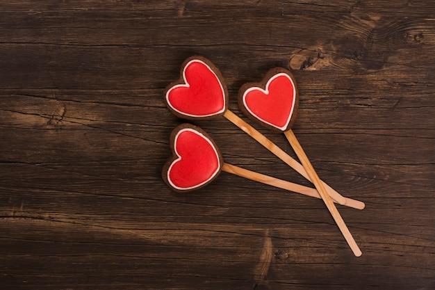 Cartão de são valentim. o coração três deu forma a pão-de-espécie sobre o fundo de madeira rústico. vista do topo
