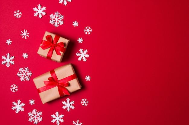 Cartão de saudação de composição de natal. presente de papel ofício em um vermelho com flocos de neve