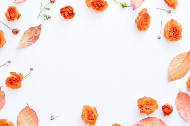 Cartão de saudação de design floral de outono folhas vermelhas e botões de rosa laranja dispostos em moldura redonda em branco