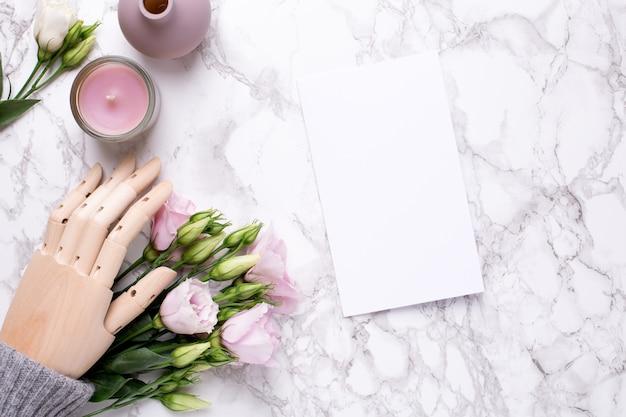 Cartão de saudação e mão de madeira com flores rosa em mármore