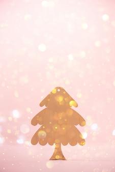 Cartão de saudação em estilo minimalista. árvore de natal de madeira no fundo cor-de-rosa com espaço da cópia, bokeh das luzes, neve.