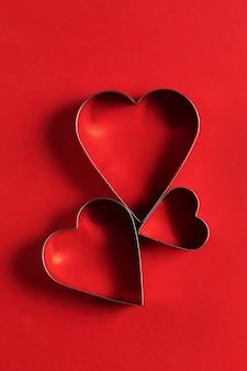Cartão de saudação minimalista do dia de são valentim, cortadores de biscoitos em forma de coração com lindas sombras, disposição plana