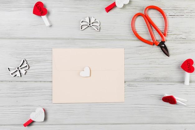 Cartão de saudação rodeado com clip de forma de coração e tesoura na mesa de madeira