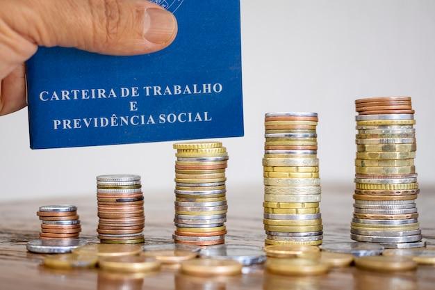 Cartão de trabalho brasileiro com pilhas de moedas na mesa. conceito de trabalho e economia