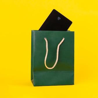 Cartão de viagem preto dentro do saco de compras de papel verde contra fundo amarelo
