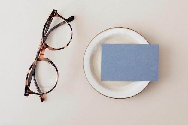 Cartão de visita azul em um prato com maquete de óculos
