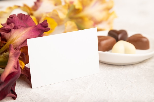 Cartão de visita branco com bombons de chocolate e flores de íris em fundo cinza de concreto. vista lateral
