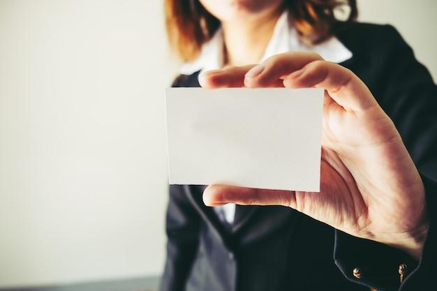 Cartão de visita branco com copo de café. trabalho de empresária adulta fundo moderno borrado de caderno de cadernos.