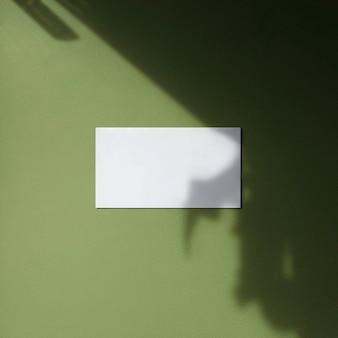 Cartão de visita branco vazio simulado com sombras de folhas