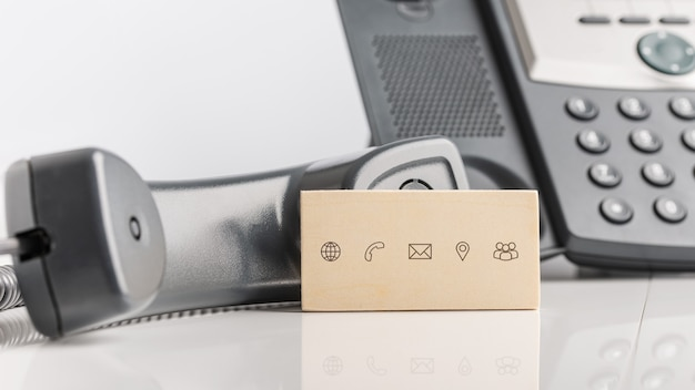 Cartão de visita com ícones de contato e comunicação apoiado no telefone fixo preto com o fone fora do gancho