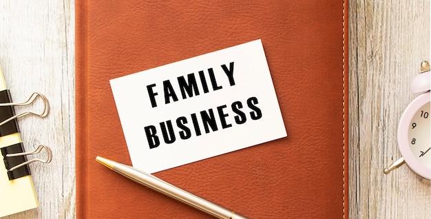 Cartão de visita com o texto empresa familiar em uma mesa de madeira