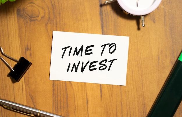 Cartão de visita com o texto hora de investir encontra-se em uma mesa de escritório de madeira