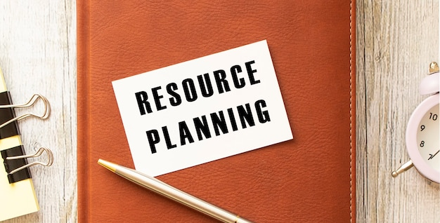 Cartão de visita com o texto planejamento de recursos em uma mesa de madeira