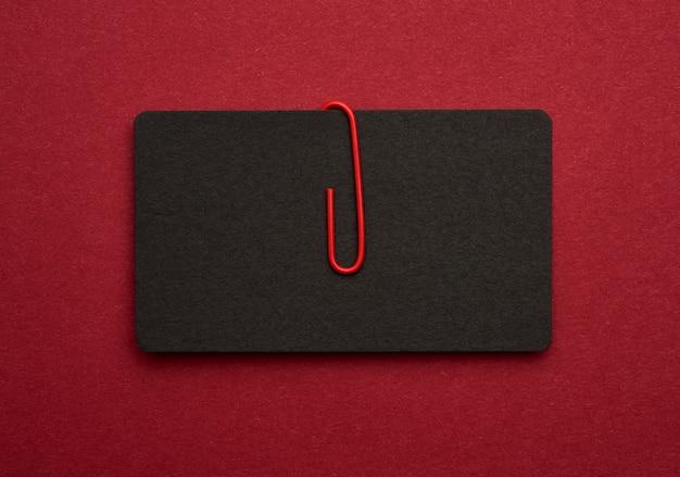Cartão de visita de papelão de papel preto e clipe de papel de metal vermelho