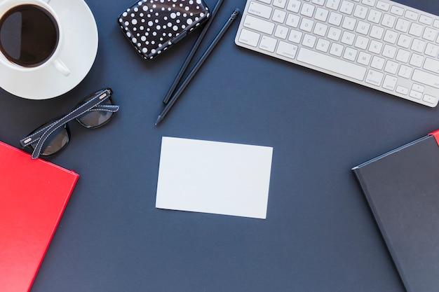 Cartão de visita e artigos de papelaria perto da xícara de café e teclado