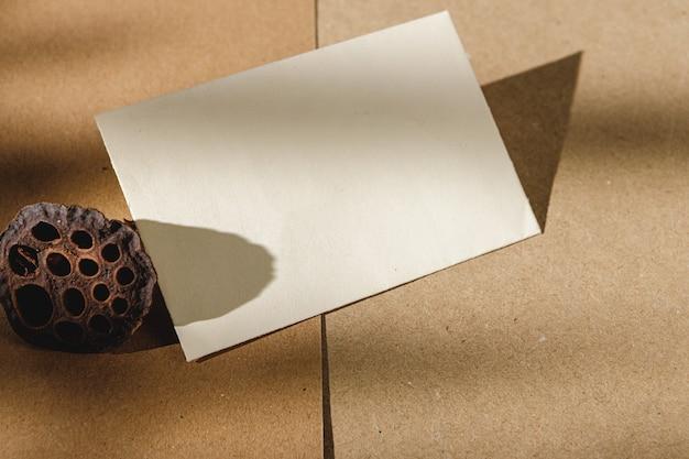 Cartão de visita e flor seca em papel bege