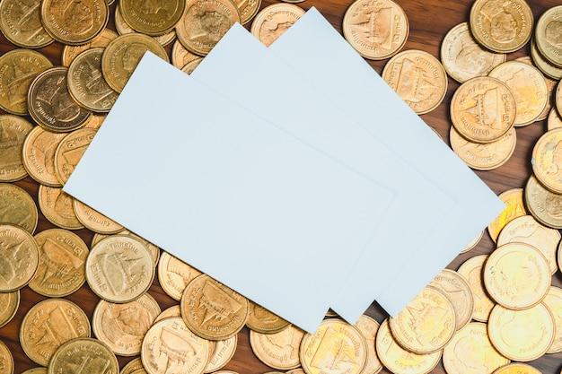 Cartão de visita em branco com pilha de moedas
