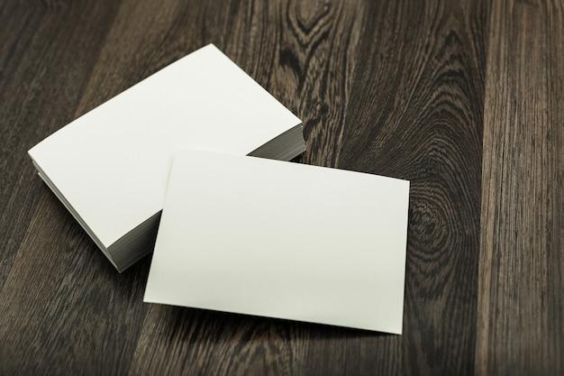 Cartão de visita em branco na mesa de textura de madeira