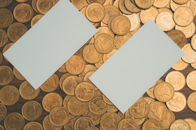 Cartão de visita em branco ou cartão de nome na pilha de moedas