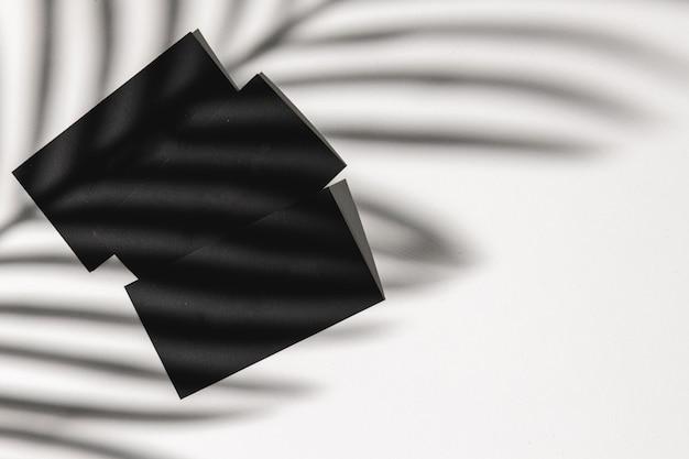 Cartão de visita em fundo de papel com sombra de folhagem