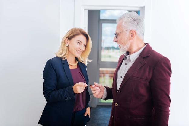 Cartão de visita. mulher de negócios linda sorridente usando um traje azul elegante e dando seu cartão de visita a um homem influente