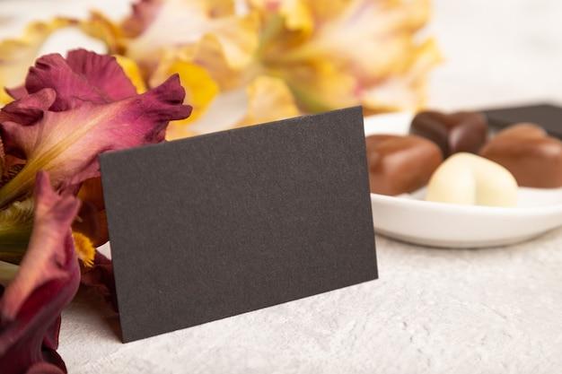 Cartão de visita preto com bombons de chocolate e flores de íris em fundo cinza de concreto. vista lateral