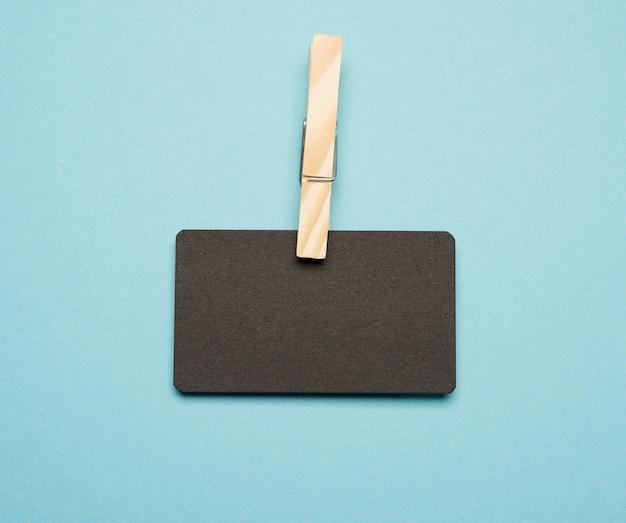 Cartão de visita retangular vazio de papel preto com prendedores de roupa de madeira