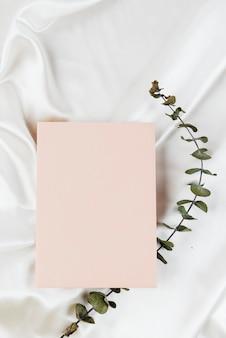 Cartão de visita rosa em fundo de têxteis